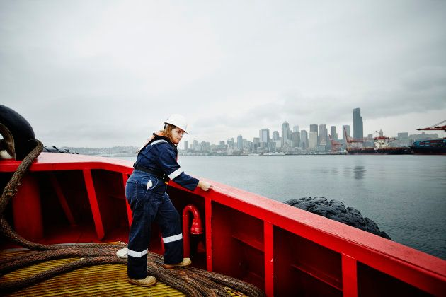 Female naval architect in hardhat and coveralls taking measurement along bulwark of commercial