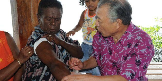 パラオのゲルール島で、回復者から話を聞く筆者(右)。