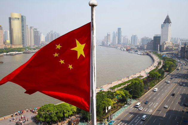 Chinese flag overlooking cityscape, Shanghai, China (Photo: Rolf Bruderer/Getty