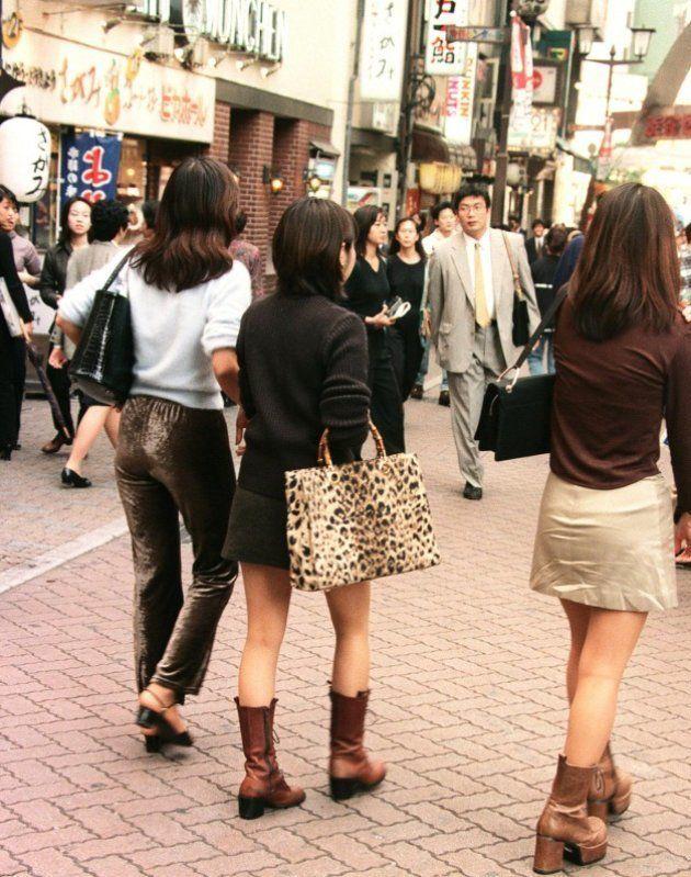 ミニスカートに靴底の厚いロングブーツ、茶髪のロングヘアーに細い眉毛といった「コギャル」ファッションが流行(東京・渋谷区=1996年10月4日撮影)