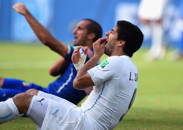 ワールドカップ・ブラジル大会で、イタリア選手(奥)に噛みついたにもかかわらず、自らが痛がる仕草をみせるウルグアイのスアレス=2014年6月24日、ブラジル・ナタール