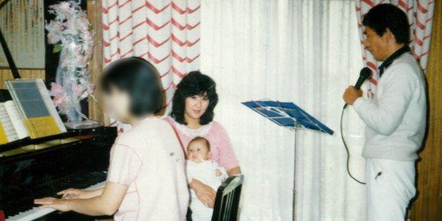 自宅でカラオケを歌う健治と、長女を抱く真須美。