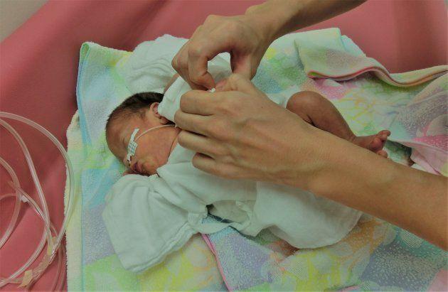 チューブをつけたまま、初めてのお風呂に。一緒に写った母親の手が大きく見える