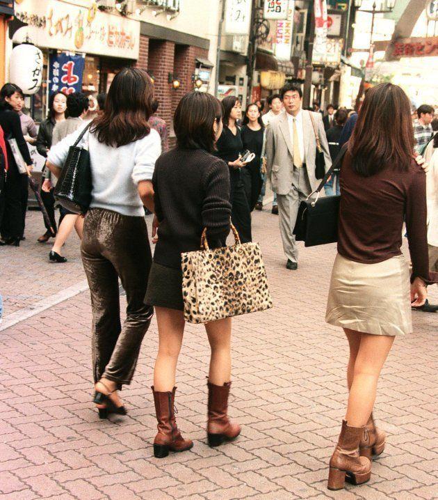ミニスカートに靴底の厚いロングブーツ、茶髪のロングヘアーに細い眉毛といった「コギャル」ファッションが流行(1996年10月4日撮影)