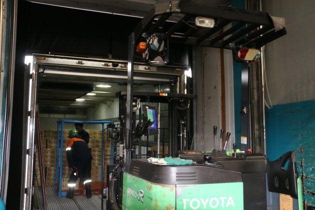 冷凍トラックから商品を出し、倉庫内に搬入する。フォークリフトには『ラグド』が固定されている。