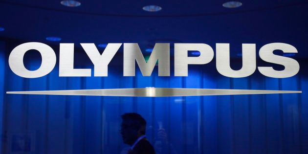 A man walks behind a logo of Japan's Olympus Corp at the company headquarters in Tokyo April 3, 2012....