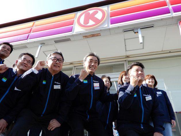 ファミリーマートへのブランド統合に伴い、閉店したサークルK店舗前で記念撮影に応じる沢田貴司ファミマ社長(中央)ら=2018年11月29日、愛知県一宮市