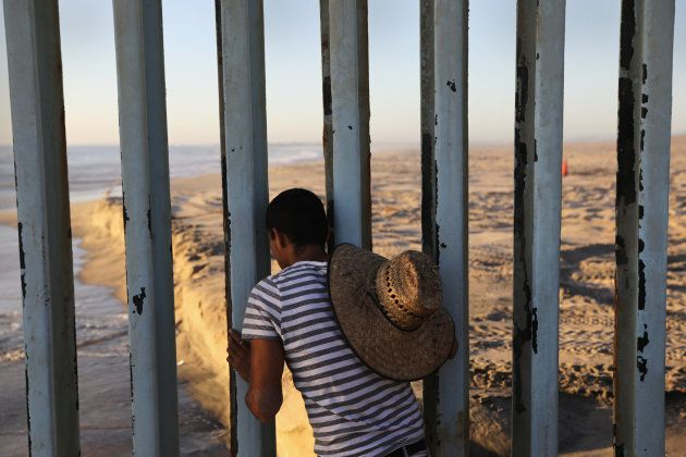 TIJUANA, MEXICO - SEPTEMBER 25: A man looks through the U.S.-Mexico border fence into the United States...