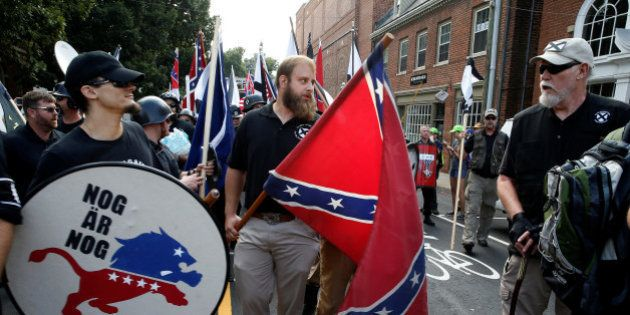 White supremacists carry a shield and Confederate flag as they arrive at a rally in Charlottesville,...