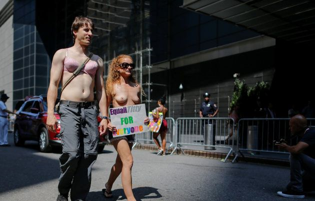 People take part in a march to celebrate the 10th anniversary of the International Go Topless Day at...