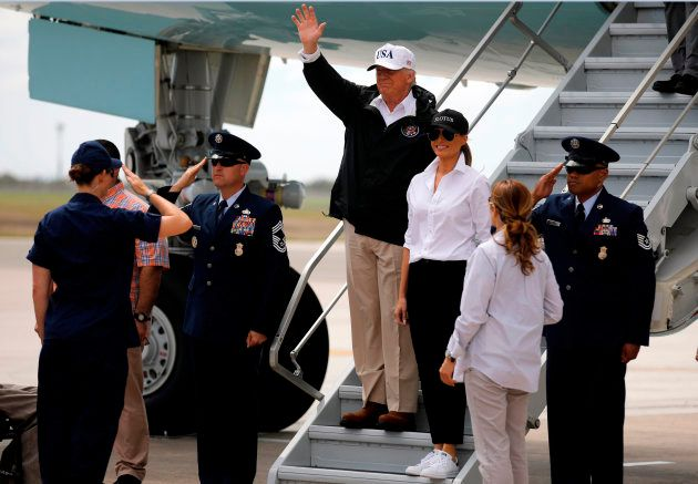 U.S. President Donald Trump (C) waves next to first lady Melania Trump upon arrival prior to receiving...