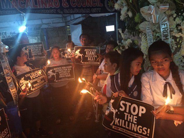 超法規的殺人に抗議するプラカードを掲げる参列者ら