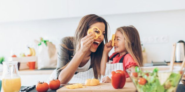 Mother and daughter having fun with the vegetables in the