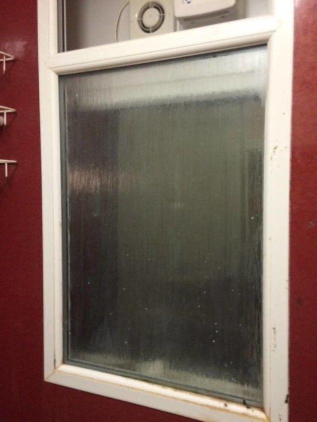 トイレの窓。隙間にティッシュペーパーに包まれた物体が見える。