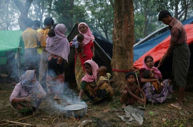 Rohingya refugees go about their day outside their temporary shelters along a road in Kutupalong, Bangladesh,...