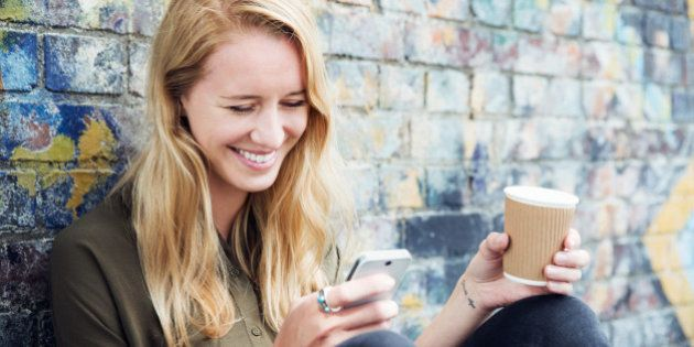 Young woman with smart phone and coffee.