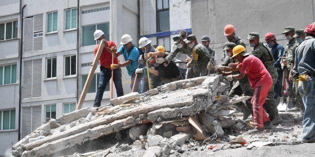 メキシコ市で20日、建物のがれきを撤去する人たち