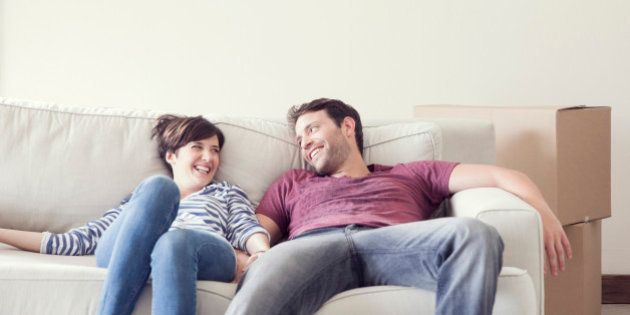 Couple relaxing on sofa while moving