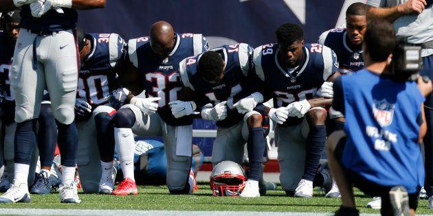 国歌斉唱の際、膝をついて起立を拒否するニューイングランド・ペイトリオッツの選手たち=9月24日、マサチューセッツ州
