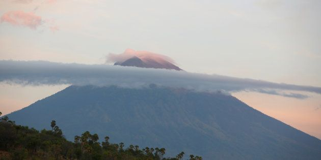 A view of Mount Agung, a volcano on the highest alert level, as the sun rises from Amed on the resort...