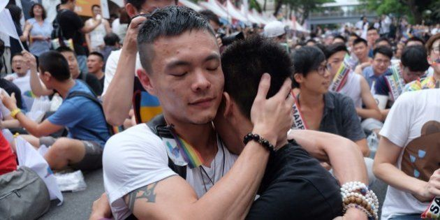 Same-sex activists hug outside the parliament in Taipei on May 24, 2017 as they celebrate the landmark...