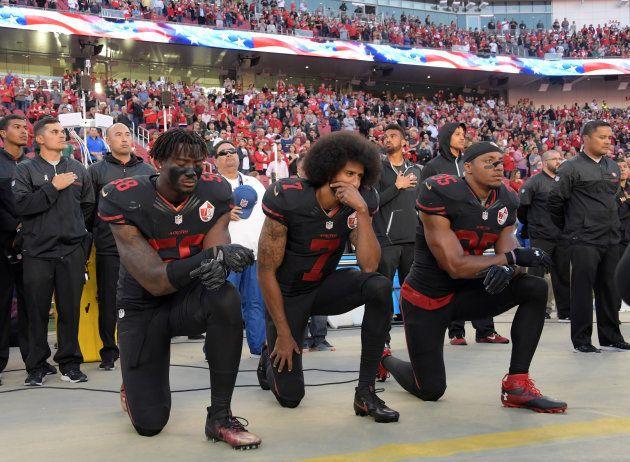 国歌斉唱時に起立せず、しゃがんで抗議の意思を示したコリン・キャパニック選手(中央)=2016年10月6日、カリフォルニア州