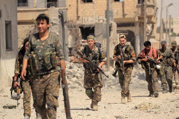市街地を進むシリア民主軍の兵士ら=ラッカ、8月9日