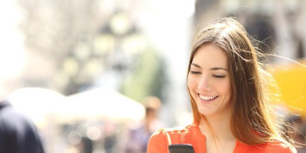 Woman wearing orange shirt texting on the smart phone walking in the street in a sunny