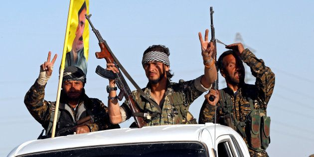 Fighters of Syrian Democratic Forces make the V-sign as their convoy passes in Ain Issa, Syria October...