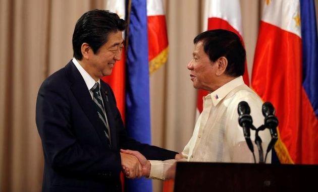 Philippine President Rodrigo Duterte and visiting Japanese Prime Minister Shinzo Abe shake hands after...