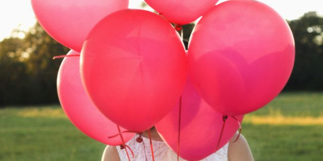 Mixed race woman with pink balloons in