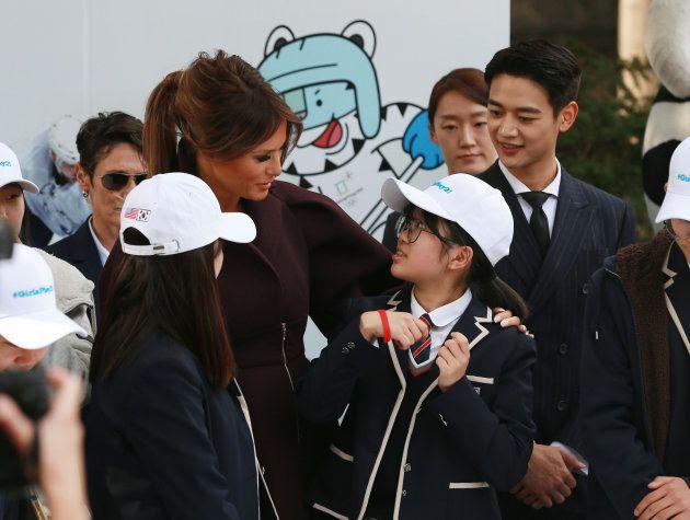 中学生と話をするメラニア夫人と、それを見守る『SHINee』ミンホ。