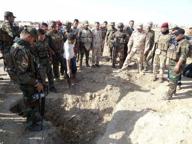 ISに処刑されたとみられる人たちの遺体が見つかった場所を調べるイラク軍兵士ら=11月11日、イラク北部ハウィジャ