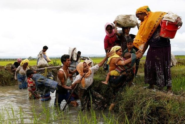 A group of Rohingya refugees cross a canal after travelling over the Bangladesh-Burma border in Teknaf,...