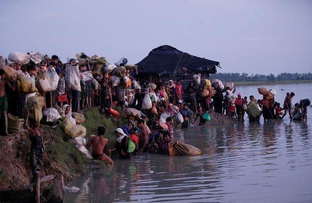 Rohingya refugees walk after crossing the Naf River at the Bangladesh-Myanmar border in Palong Khali,...