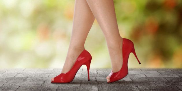 Woman legs in red high heels walking on urban