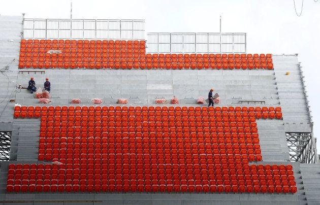 建設作業員らが朱色の座席を取り付ける仮設スタンドの工事現場
