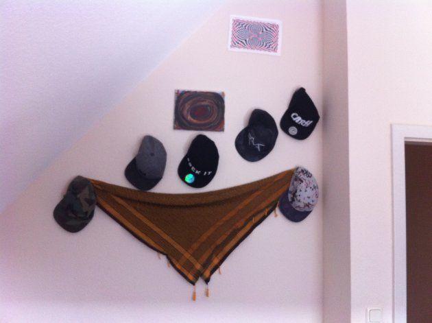 ラマットはキャップの収集が趣味。壁にはコレクションが飾られる。部屋の隅には実母の写真もあった。