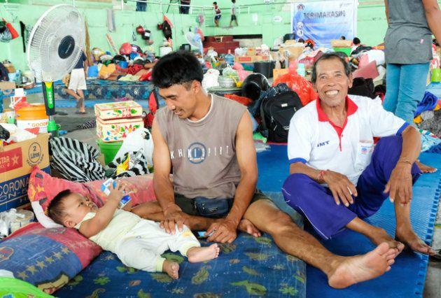 インドネシア・バリ島で噴火したアグン山の近くから約1カ月前に避難し、家族10人で避難所暮らしを続けているというワヤン・スムルティさん(右)ら=11月29日、バリ島中部クルンクン、朝日新聞社撮影