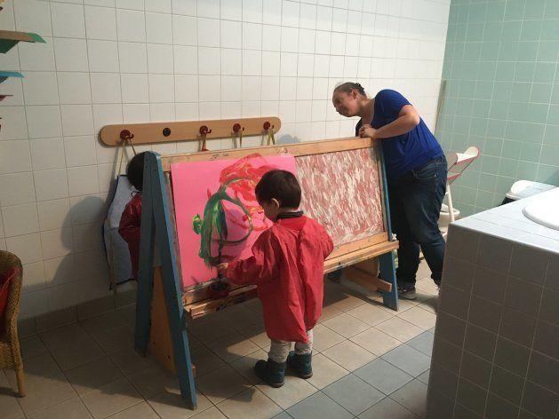 保育場所は保育室に限らない。ここでは浴室横の更衣室を活用。お絵描き台を置き、2歳児2名が保育士1名と水彩をしている。可能な限り少人数でグループ分けをし、保育士・児童ともに集中できる時間を作るという。