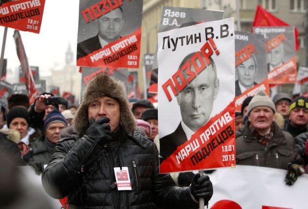 プーチン政権を批判する野党勢力の集会。プラカードにはプーチン氏や与党議員らの写真が印刷されており、「恥」と書かれている=2013年1月、モスクワ