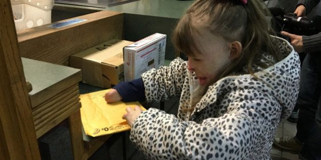 CORRECTS YEAR TO 2015, NOT 2013 - Safyre Terry, 8, opens a gift Wednesday, Dec. 9, 2015, at a post office...