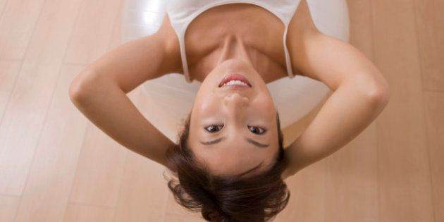 Young woman practising on balance ball