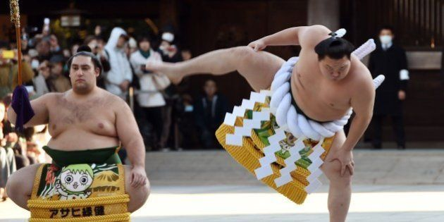 Mongolian-born sumo grand champion, or 'yokozuna', Hakuho (R) performs a ring-entering ceremony beside...