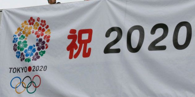 Workers hang a banner celebrating the city's successful bid to host the 2020 Summer Olympics as they...