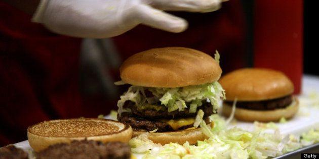 An employee prepares burgers at a Fatburger outlet in Karachi, Pakistan, on Saturday, Jan. 5, 2013. Fatburger...