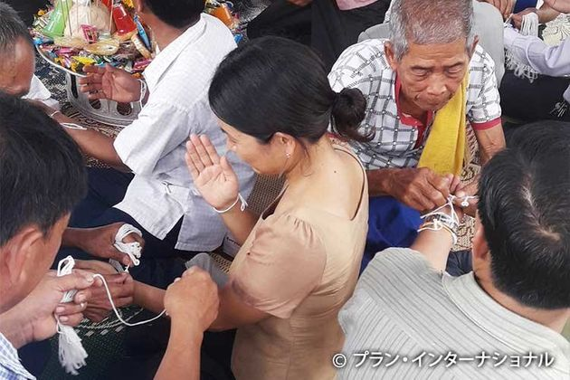 健康を祈願するために、腕に白い糸を巻いてもらいます