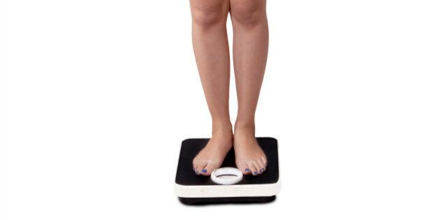 Full length of teenage girl with casual clothes measure her weight with weight scales
