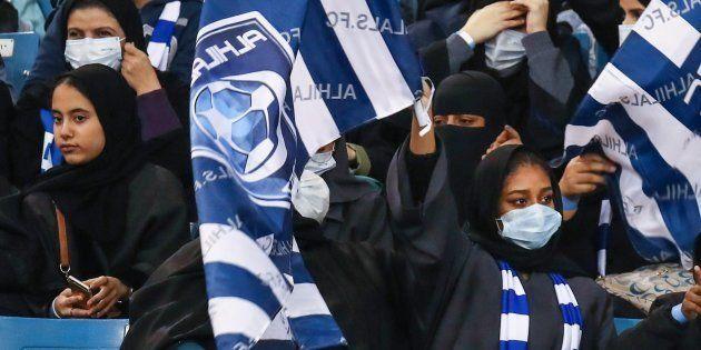 競技場でのサッカー観戦が許され、応援するチームの旗を振るサウジアラビアの女性ら=2018年1月、リヤド