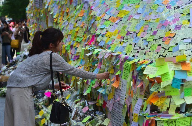 South Koreans leave messages written on post-it notes at an exit of Gangnam subway station, which has...